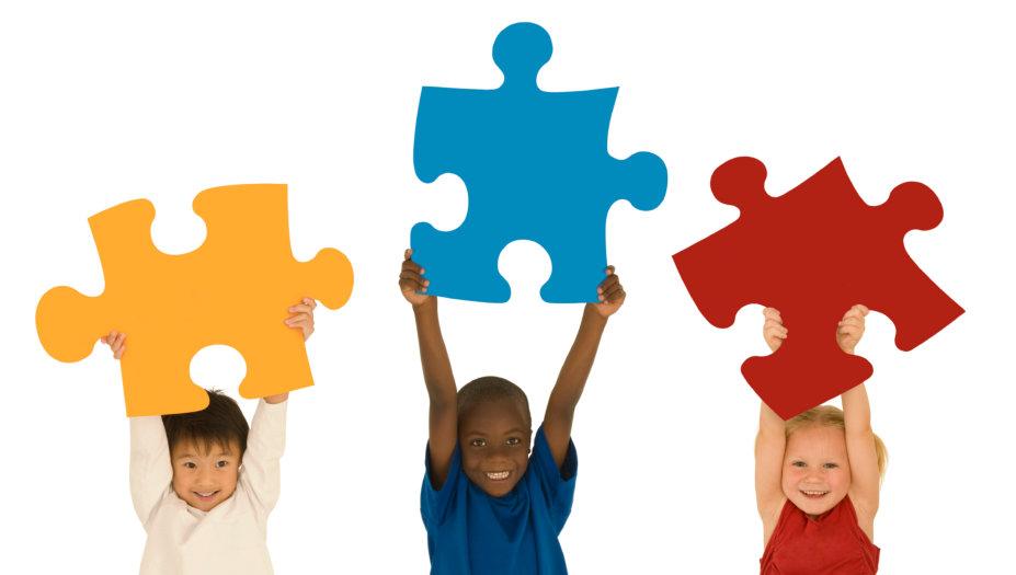 three children raises big jigsaw puzzle pieces