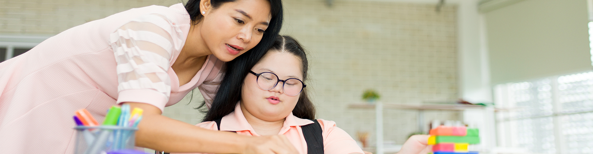 woman helping girl with puzzle